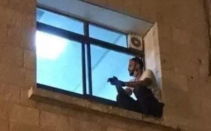 Foto de Jihad Al-Suwaiti trepado en la ventana de un hospital