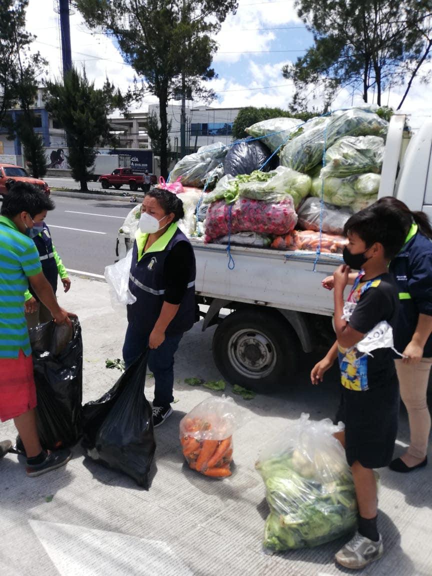 Vecinos de Mixco con banderas blancas reciben raciones de verduras